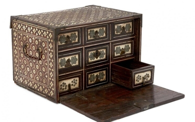 A Mughal ivory-inlaid wooden chest, Northwest India, 17th century, of rectangular form with fall front revealing six drawers with applied openwork polychrome lattice panels surrounded by borders of inlaid ivory rosettes, large central drawer with...
