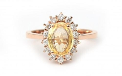 An 18 karat rose gold sapphire and diamond cluster ring. Featuring an oval cut yellow sapphire of ca. 1.50 ct. in a surround of fifteen brilliant cut diamonds of ca. 0.40 ct. in total, ca. G-H, ca. VS. Gross weight: 4.7 g.