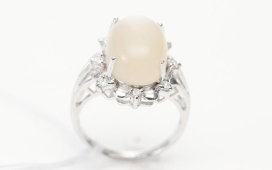 A MOONSTONE AND DIAMOND DRESS RING IN 18CT WHITE GOLD, CENTRALLY SET WITH AN OVAL CABOCHON CUT MOONSTONE OF 9.58CTS, IN A BORDER OF...