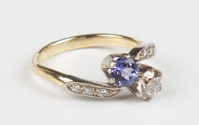 A gold, tanzanite and diamond ring in a crossover design, claw set with a circular cut diamond and a