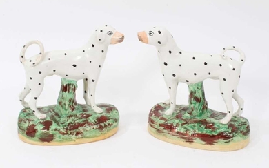 Pair of Staffordshire pottery models of Dalmatians, shown standing on naturalistic bases, 16cm high