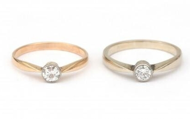 Two gold similar diamond solitaire rings. One set with a old brilliant cut diamond of 0.20 ct., ca. G-H, ca. VS in 14 krt white gold shank, maker's mark *TB5* for Bierhuijs, Th. 1964-1981, Rotterdam, The Netherlands. The other ring is set with an old...