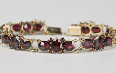 A 9ct gold and garnet bracelet, each link claw set with three oval cut garnets and four smaller circ