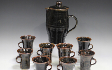 A Jeremy Leach Lowerdown pottery coffee pot and eight mugs, 1970s, each covered in a tenmoku glaze