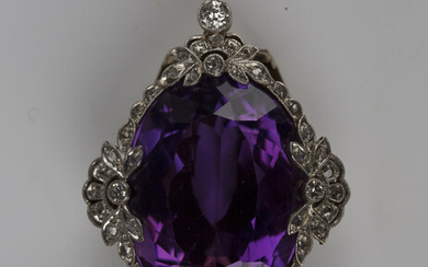 A gold, platinum, amethyst and diamond clip, mounted with the large oval cut amethyst within a diamo