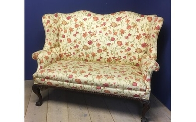 Early C20th upholstered winged settee with polished mahogany...