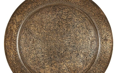 A brass tray with an unusual design, India, 19th century, of shallow form with wide rim, decorated with an extremely dense design of swarms of animals and birds either side of a river, with a woman at the centre blowing a large horn, 30.2cm. diam.