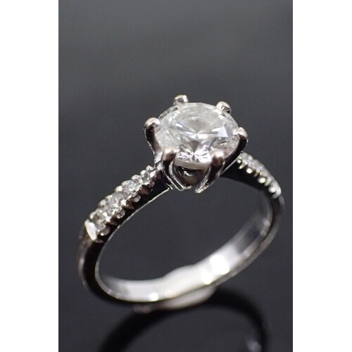 A diamond single stone ring set with diamond shoulders in 18...