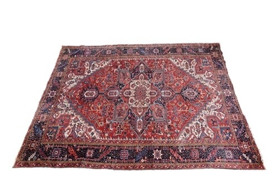 Persian Heriz carpet, crimson field centred with a fawn and ...