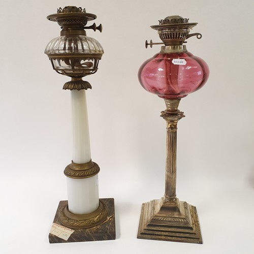 A silver plated oil lamp, with a cranberry glass well, 56 cm...