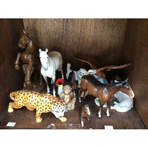 A collection of assorted ceramic animal figures, predominant...