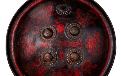 A lacquered rhino hide shield with figurative decoration, Rajasthan, India, late 18th century, of circular form, the monochrome figural decoration arranged around four applied bronze bosses depicting various deities interspersed with exuberant...