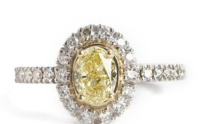 A diamond ring set with a fancy intense yellow diamond weighing app. 0.81 ct. encircled by numerous diamonds, mounted in 18k white gold. G-H/SI-P1. Size 53. GIA – Bruun Rasmussen Auctioneers of Fine Art