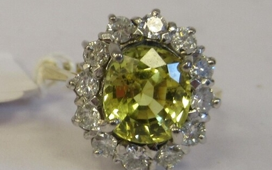 An 18ct gold cluster ring, claw set with a mild yellow Ceylo...