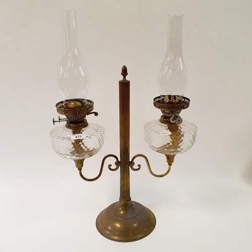 A brass double oil lamp, with clear glass wells, 65 cm high