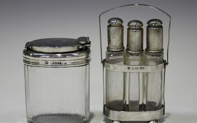 A set of three George V silver topped glass scent bottles, interfitting in a silver stand with swing