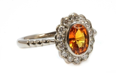 An 18ct white gold orange sapphire and diamond oval cluster ring