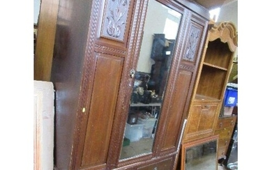 An Edwardian mirror door wardrobe, with carved decoration an...