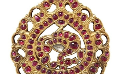 An exceptional ruby-set gold peacock pendant, South India, 18th century, of drop form, with two suspension loops, the bird with a diamond to its back and on an openwork ground, the whole within a frame of small rubies, the border a scrolling...