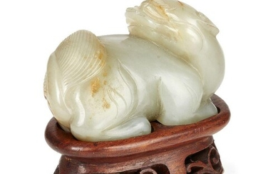 Property of a Gentleman (lots 36-85) A Chinese celadon green and russet jade lion dog, 17th century, in recumbent pose with head turned over its right shoulder, with finely detailed brows and broad tail, 6.5cm long, later fitted wood stand...