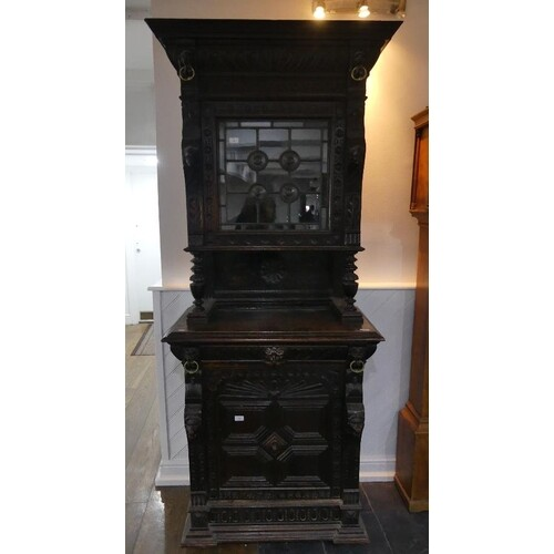 A Victorian Jacobean style carved oak upright Cabinet, with ...