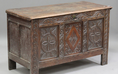A late 17th/early 18th century oak coffer, the hinged lid above a carved triple panel front, on stil