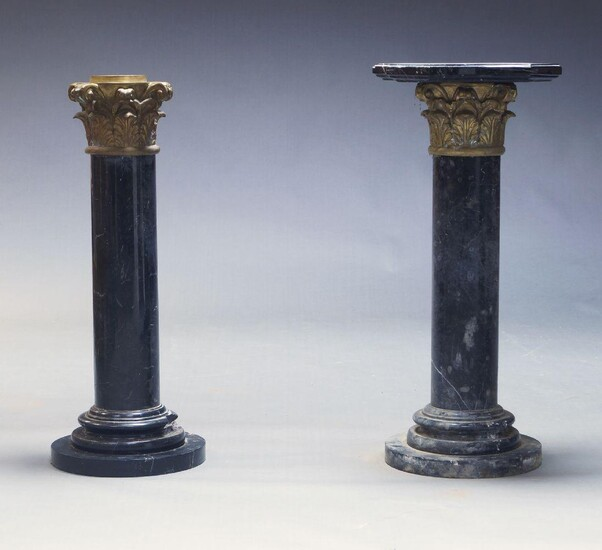A pair of black and white variegated marble columns, 20th Century, with shaped top (one lacking top) above gilt metal Corinthian capitals, the cylindrical column on circular base, 90cm high (2)