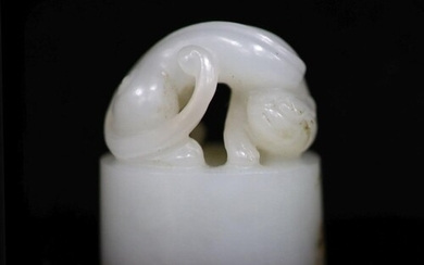 A Chinese white jade oval seal, carved in high relief and op...