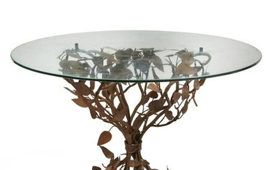 A wrought iron and tole shrub form garden table