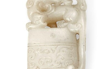 Property of a Gentleman (lots 36-85) A Chinese white and russet jade archaistic axe-form pendant, 18th century, formed as an archaistic axe surmounted with a mythical beast with head turned backwards, the stone of even white translucent tone with...