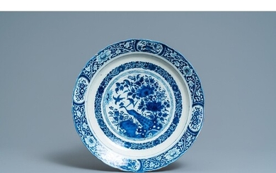 A Dutch Delft blue and white dish with a peacock in a Chines...