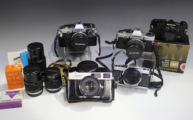 A collection of Olympus cameras and lenses, comprising OM-2 camera body, OM10 camera with Zuiko Auto