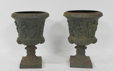 An Ornate Pair of Patinated Cast Iron Urns.