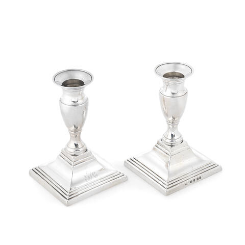 An unusual pair of George III cast silver 'push up' dwarf candlesticks