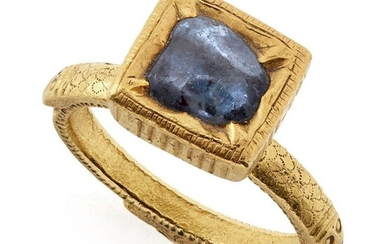 A South Indian sapphire ring, India, 18th century, the solid gold band engraved to shoulders with scale design and makara heads, the shank with a finely stippled design, the sapphire set in finely worked kundan technique with lobed edges and...