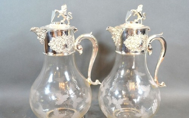 A pair of silver plated and engraved glass claret jugs, each...