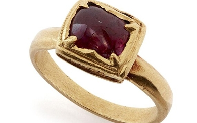 A ruby set square gold ring, South India, 19th century or earlier, the polished ruby pebble set using the kundan technique with triangular prongs in each corner securing the stone in the raised square setting, the solid gold band plain, 2.6cm...