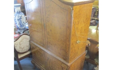 A 1950's walnut cocktail cabinet having four cupboard doors ...