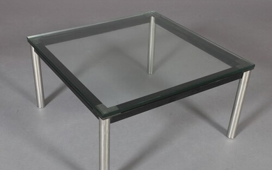 A clear glass coffee table, square, on black and chrome tubu...