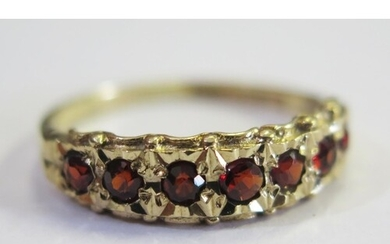 A 9ct Yellow Gold and Garnet Seven Stone Ring, size Q, 2.2g
