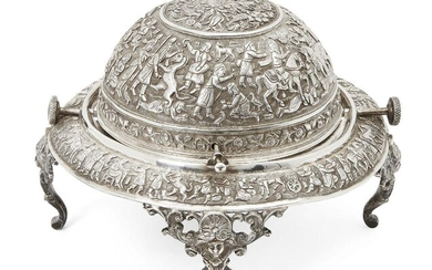 A Qajar engraved silver serving dish, Iran, late 19th-early 20th century, on three openwork feet with face, elaborately decorated to exterior with Achaemenid revival scenes the top of the dome with flowers and birds within a roundel, 25cm. diam...