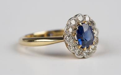 A gold, sapphire and diamond cluster ring, circa 1910, claw set with the cushion cut sapphire within