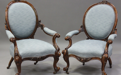 A near pair of mid-Victorian walnut showframe armchairs with finely carved decoration, each upholste