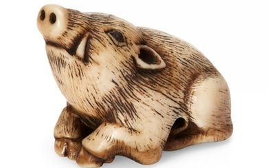 Property of a Gentleman (lots 36-85) A Japanese Ivory netsuke, 18th century, carved as a recumbent boar, Kyoto school, lying with its snout raised, eyes inlaid with dark horn, 4cm long