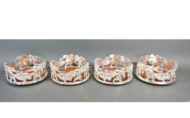 A set of four silver plated bottle coasters of pierced form ...