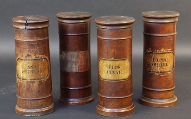 Set of four turned wood apothecary jars with interlocking lids. Paper labels. 19th century. Height 20 cm. Cracks