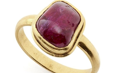 A ruby-set gold ring, South India, in a modern gold setting, the polished pebble stone of almost rectangular form, the setting with central raised ridge, plain gold band, 2.8cm. high, weight 7 grams