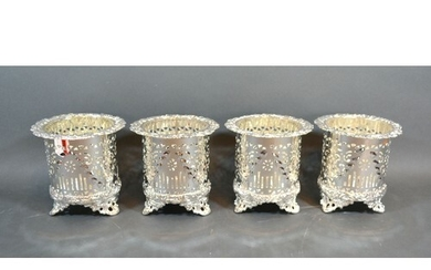 A set of four silver plated bottle coasters of pierced form,...