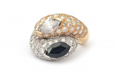 An 18 karat sapphire and diamond cross over ring. Featuring a marquise cut diamond of ca. 0.90 ct., ca. PI, ca. M-L and a marquise cut dark blue sapphire of ca. 1.12 ct. Further set with ninety pavé set brilliant cut diamonds of ca. 2.70 ct. in total...
