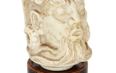 Property of a Gentleman A carved ivory cane finial, 19th century, carved as Pan depicted with eyes closed and open mouth, 6cm high, on associated socle base